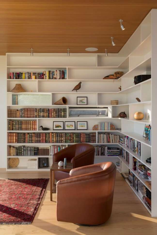 48. Sala com estante de canto planejada pra livros e enfeites – Foto Dezeen