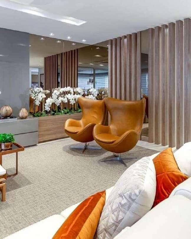 23. Decoração de sala moderna com parede espelhada e poltrona cor de caramelo – Foto: Decor Salteado