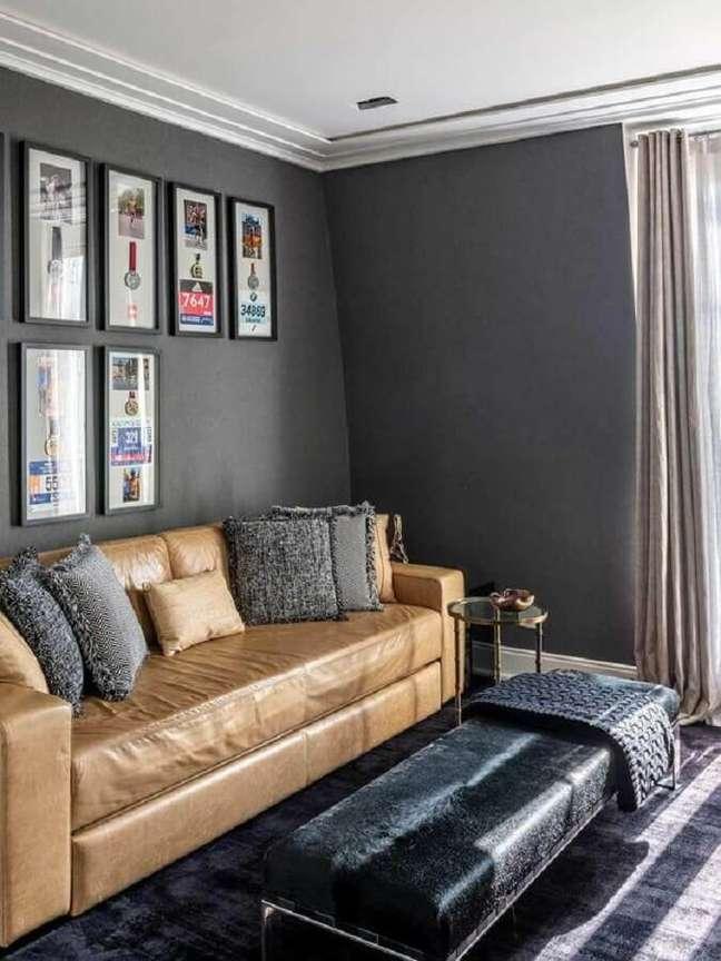 3. Decoração de sala cinza com parede de quadros e sofá cor caramelo – Foto: Casa de Valentina