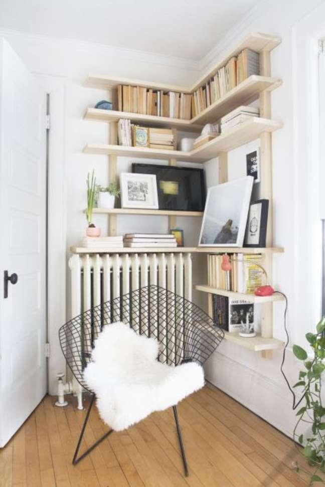 30. Estante de canto planejada com cadeira moderna perto – Foto Pinterest
