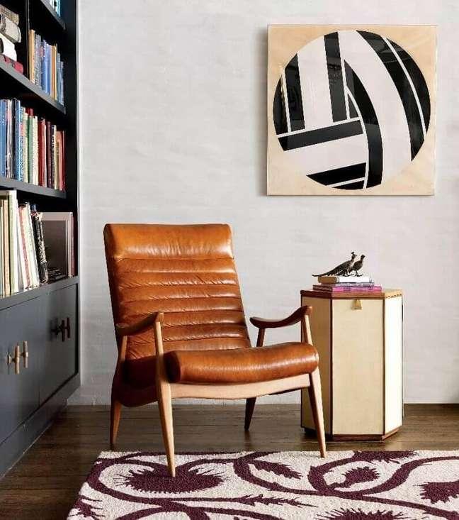21. Decoração de sala com estante de livros e poltrona cor caramelo de couro – Foto: Home Fashion Trend