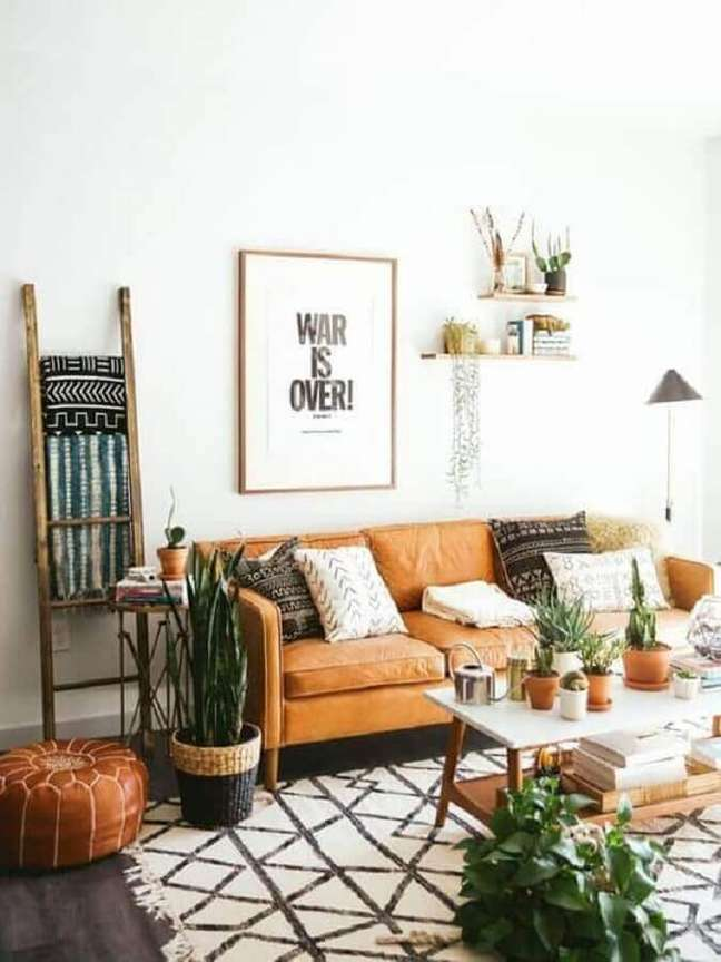 25. Decoração simples para sala branca com sofá cor caramelo e vasos de plantas – Foto: Archzine