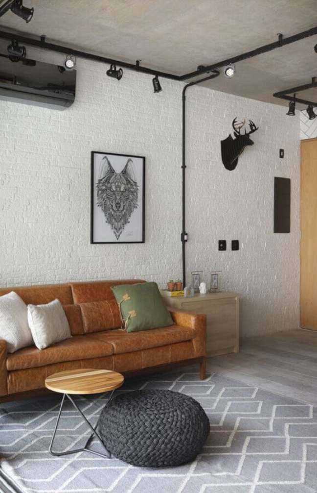 59. Sofá cor caramelo para sala estilo industrial decorada com puff de crochê cinza – Foto: Mariana Orsi
