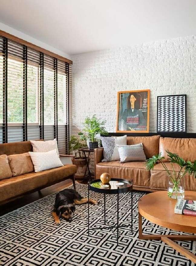 27. Parede tijolinho branca para decoração de sala com sofá cor caramelo e tapete geométrico – Foto: Casa de Valentina