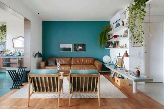 2. Sala azul e branca decorada com sofá cor caramelo e poltrona de madeira – Foto: Jeito de Casa