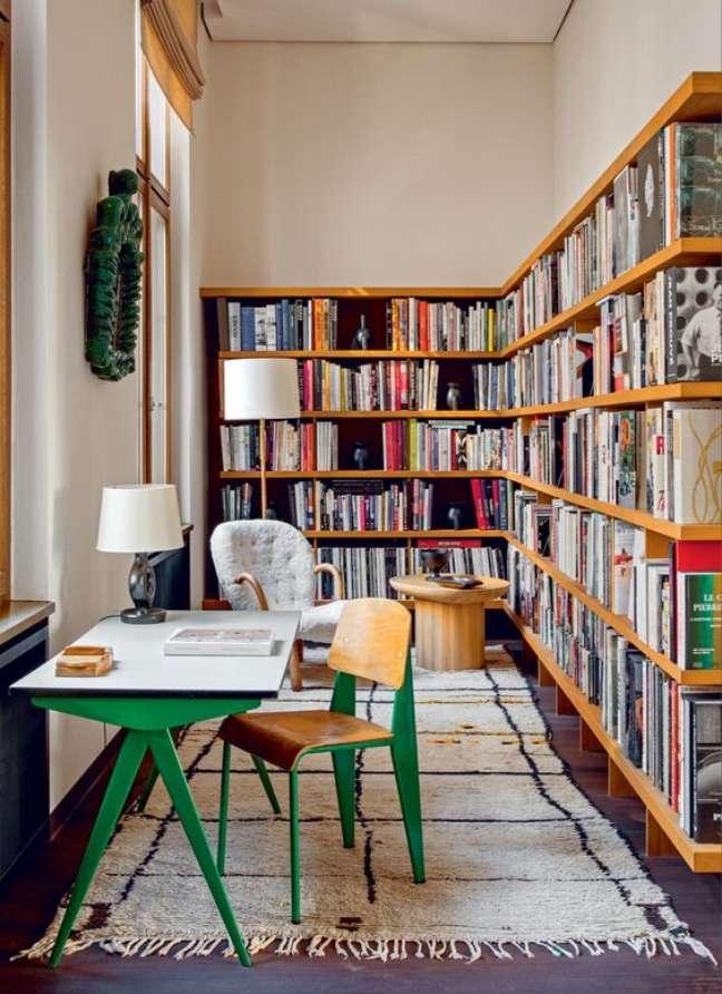 26. Estante de canto de madeira para livros variados com escrivaninha verde – Foto Architextural Digest