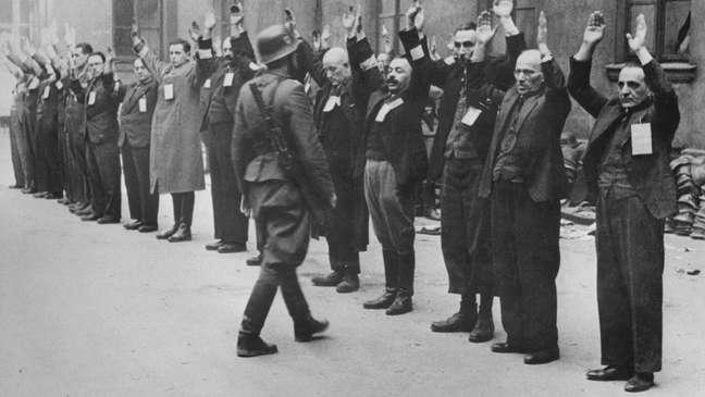 Um soldado da SS, a milícia nazista, aborda trabalhadores judeus no gueto de Varsóvia em 1943