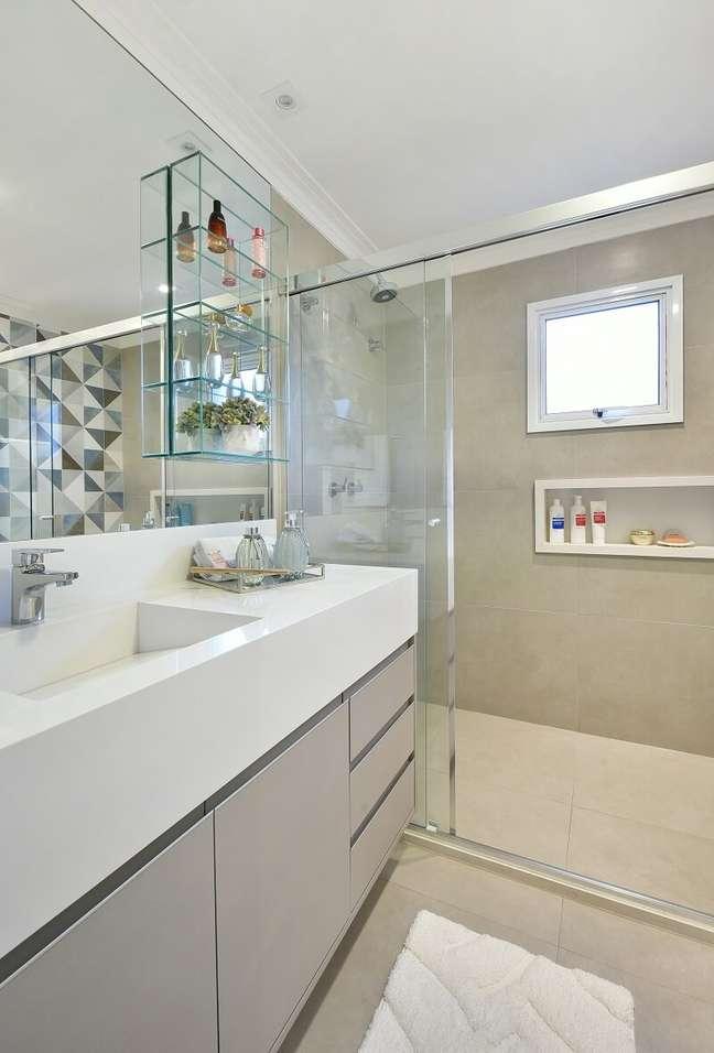 21. Gabinete cinza, cuba esculpida em mármore prime e prateleiras de vidro decoram o banheiro. Foto: Sidney Doll