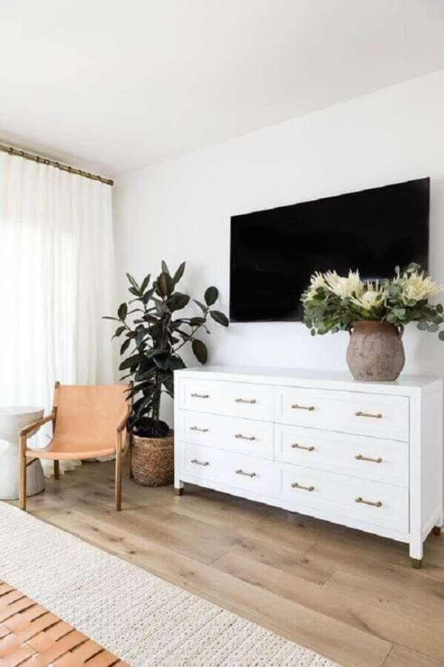 19. Cômoda branca grande para quarto amplo decorado com poltrona de madeira e vaso de planta no chão – Foto: Apartment Therapy