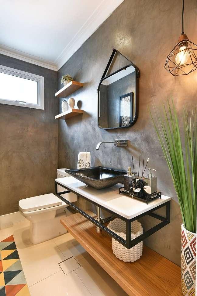 4. Parede de cimento queimado, pendente aramado e elementos em madeira decoram o lavabo do imóvel. Foto: Sidney Doll