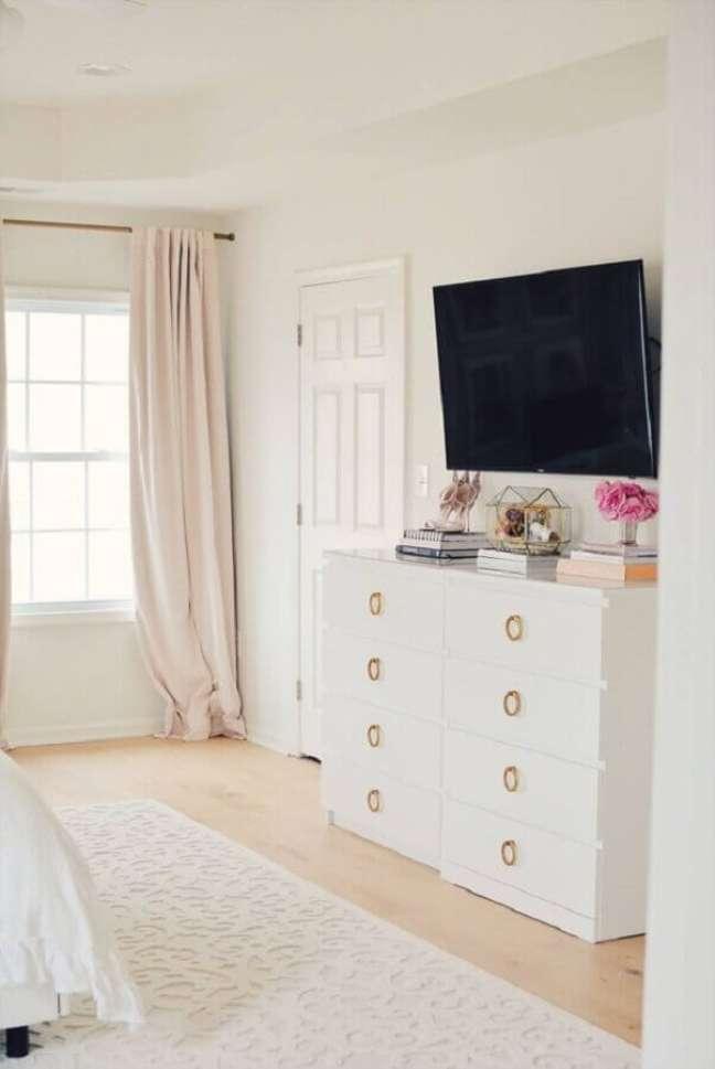 26. Cômoda branca para quarto grande decorado com TV na parede – Foto: Pinterest