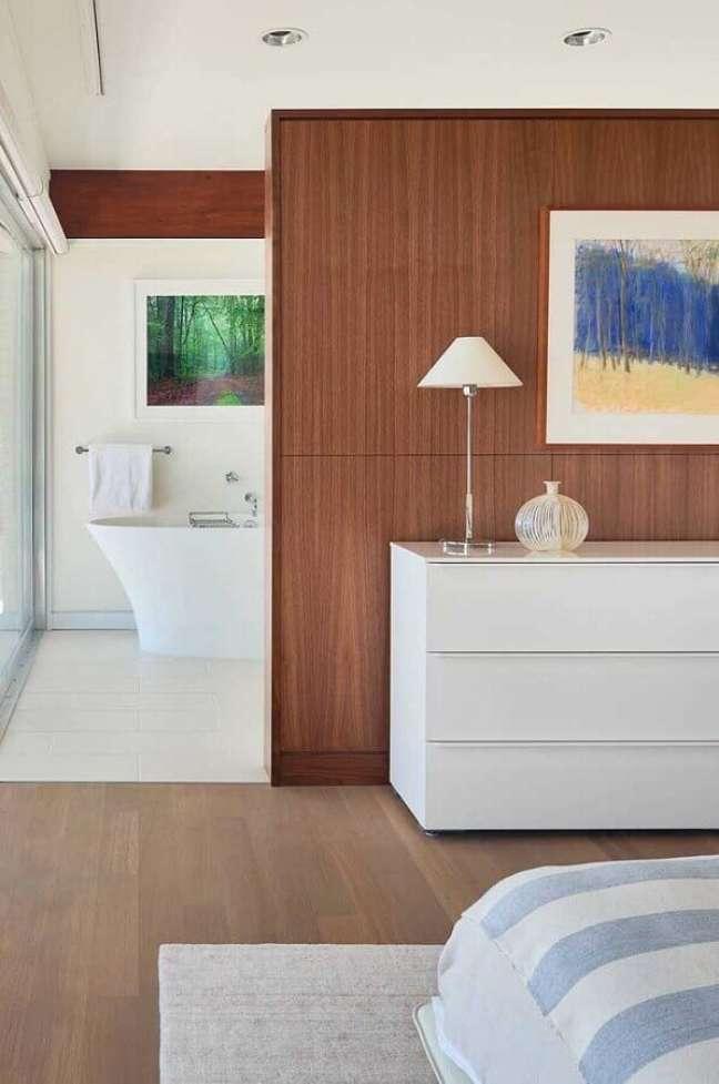 27. Cômoda branca para quarto suite decorado com parede de madeira – Foto: Jeito de Casa