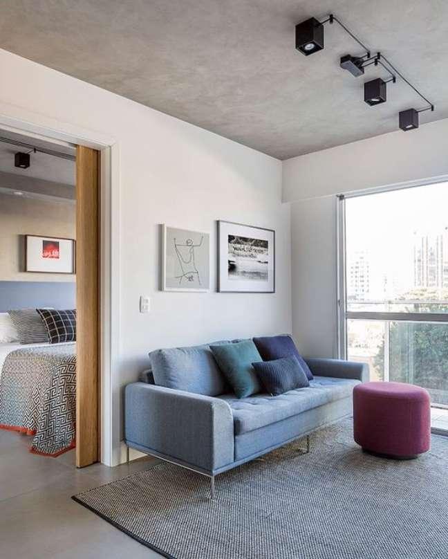 41. Sofá pé palito na cor azul com puff roxo e tapete cinza moderno – Foto Pinterest