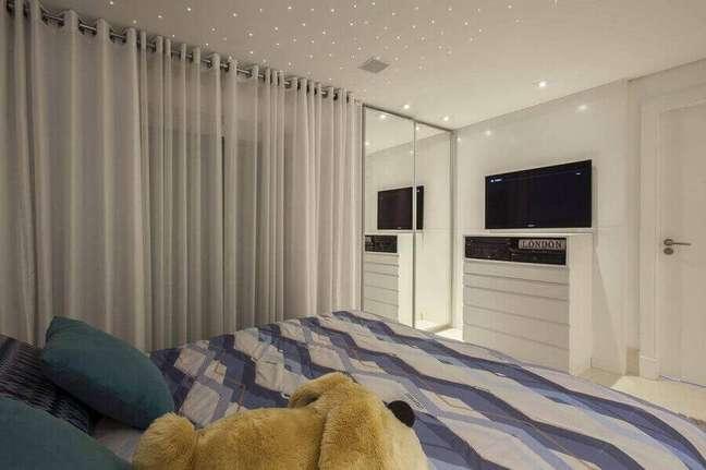 23. Cômoda branca para quarto de casal grande decorado com guarda roupa espelhado – Foto: Sandra Sanches