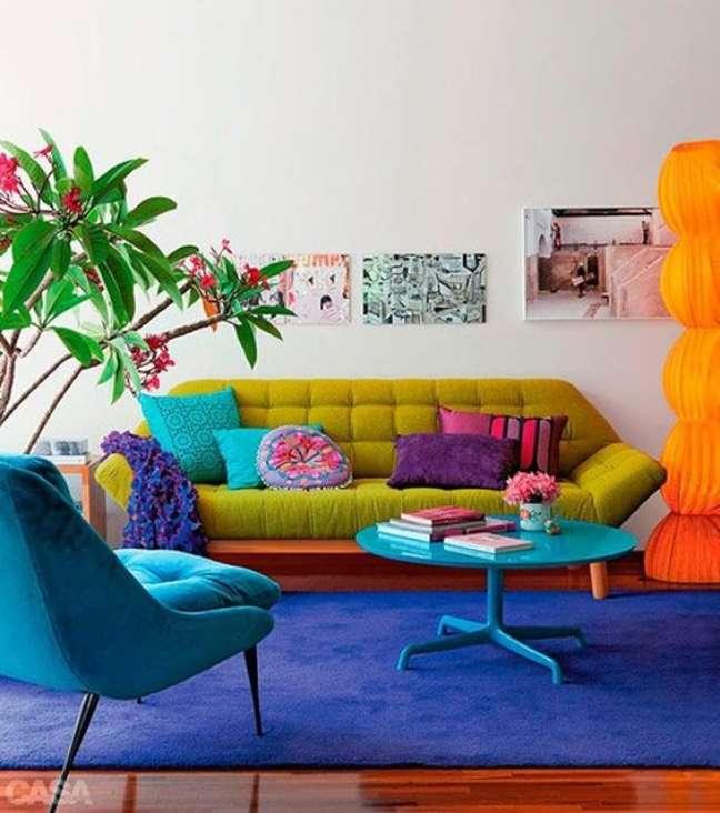 3. Sala retrô colorida com sofá pé palito verde e poltrona azul na mesma cor que o tapete – Foto casa cor