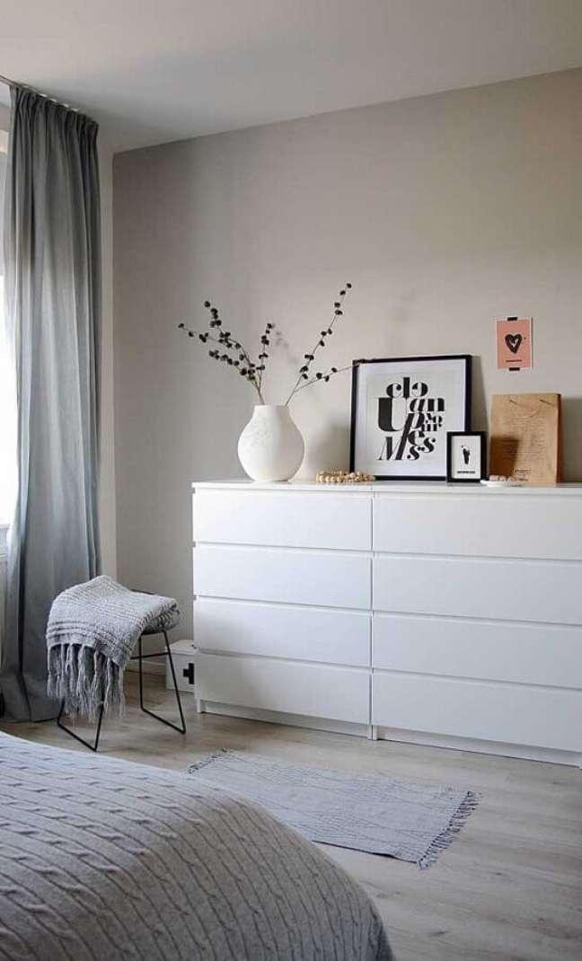 24. Cômoda branca para quarto de casal minimalista decorado com cortina cinza e piso de madeira clara – Foto: Apartment Therapy