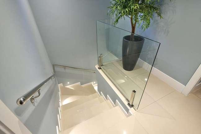 11. Escada de mármore e guarda corpo de vidro leva ao andar superior do imóvel. Foto: Sidney Doll