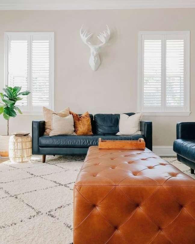 44. Sala com sofá de couro com pé palito e puff capitonê – Foto Pinterest