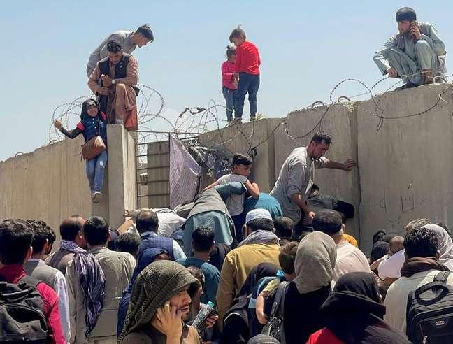 Homem puxa menina para entrar no aeroporto de Cabul, no Afeganistão 16/08/2021 REUTERS/Stringer