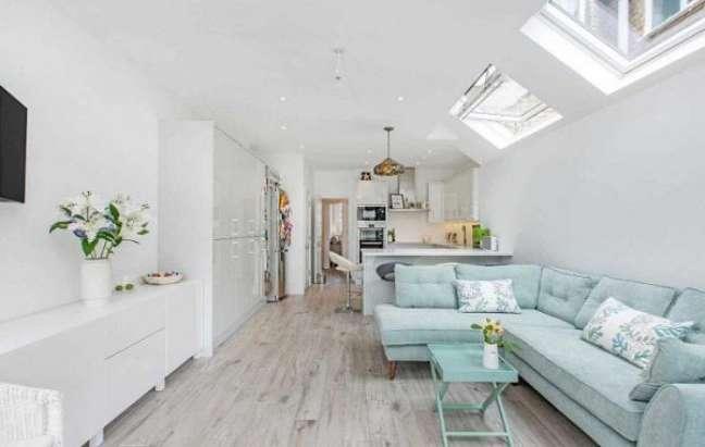22. Sala minimalista e branca com sofá pé palito na cor azul claro – Foto Ashley gray