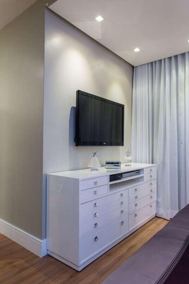 25. Cômoda branca para quarto decorado em cores claras com TV na parede – Foto: Bruno Sgrillo