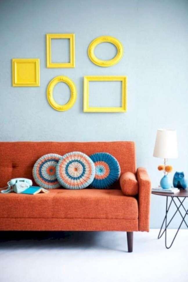 16. Sala com moldura colorida amarela e sofa pé palito na cor salmão – Foto Pinterest