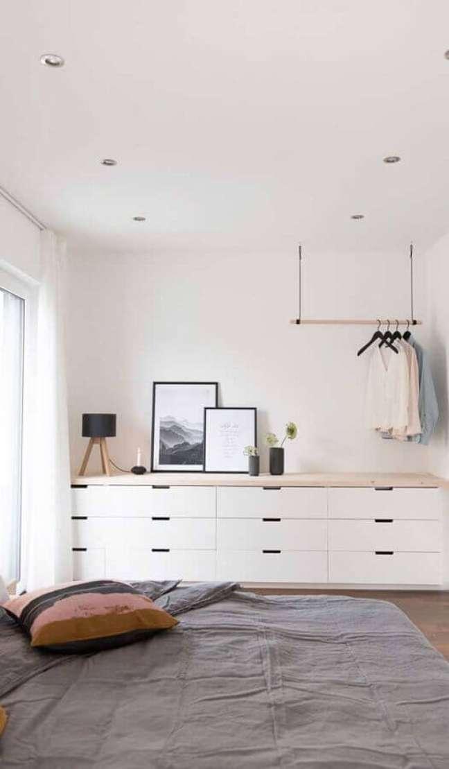 6. Cômoda branca grande para quarto de casal minimalista decorado com cabideiro de teto – Foto: Pinterest