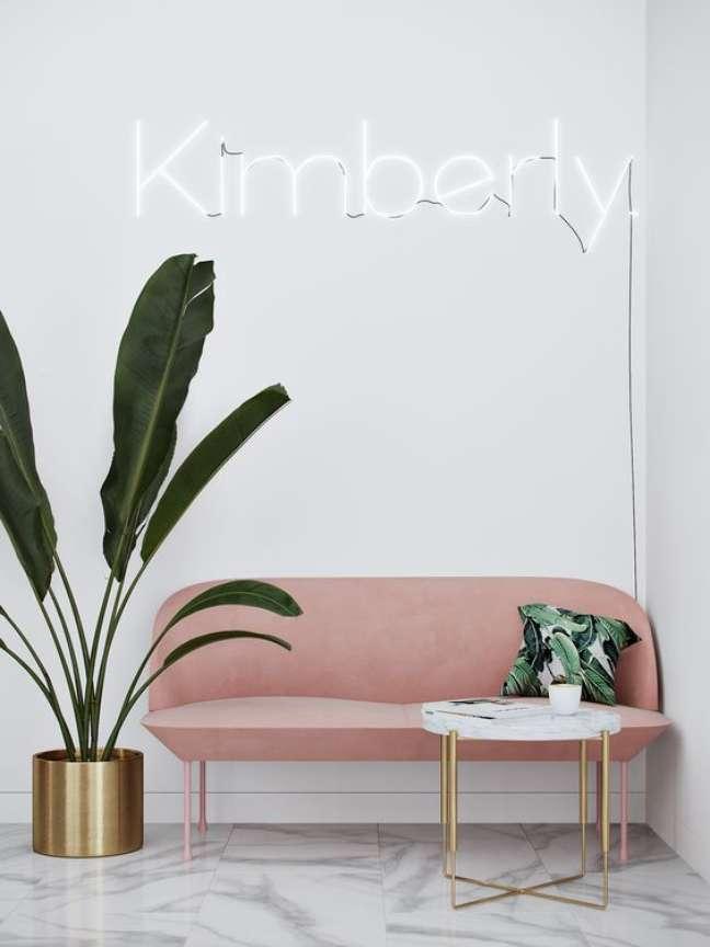 18. Sala de espera pequena com sofá pé palito rosa e vaso de plantas grandes – Foto Behance