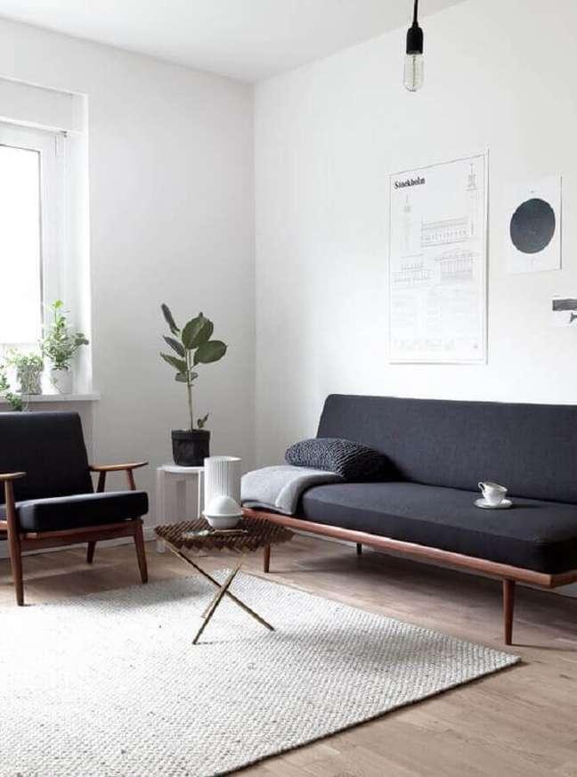 20. Sala decorada com sofá pé palito e poltrona preta de madeira – Foto Arkpad