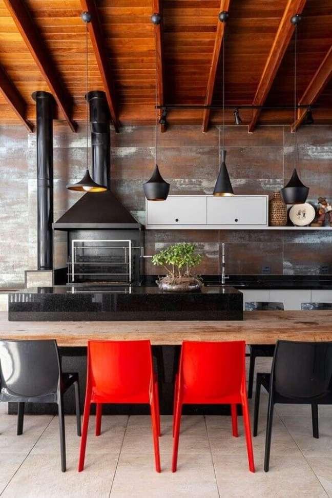 40. Lustre para área gourmet externa decorada com bancada de madeira e cadeiras vermelhas e pretas – Foto: Fashion Bubbles