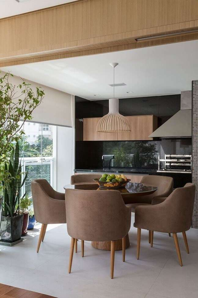 38. Lustre para área gourmet decorada com mesa redonda e churrasqueira – Foto: Casa de Valentina