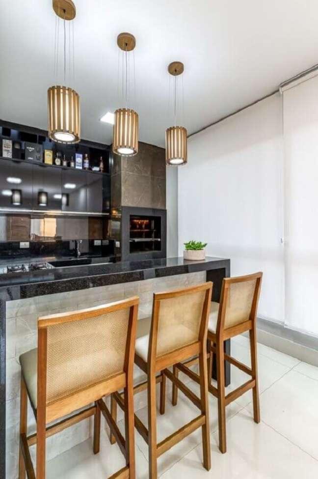 52. Lustre pendente para área gourmet decorada com banqueta de madeira para bancada preta – Foto: RP Guimarães