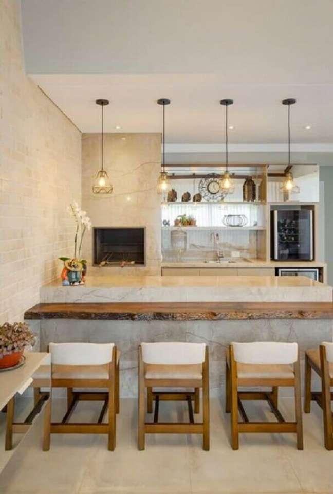 25. Decoração em cores neutras com lustre pendente para área gourmet com bancada de madeira rústica – Foto: Architrends