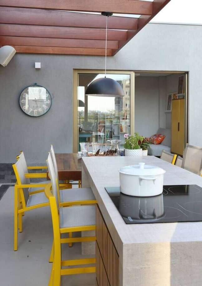 42. Lustre para área gourmet externa decorada com cadeiras pretas para ilha com cooktop – Foto: Pinterest
