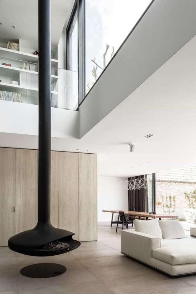 24. Lareira suspensa preta perto do sofá branco na sala de estar de conceito aberto – Foto Abs Bouwteam