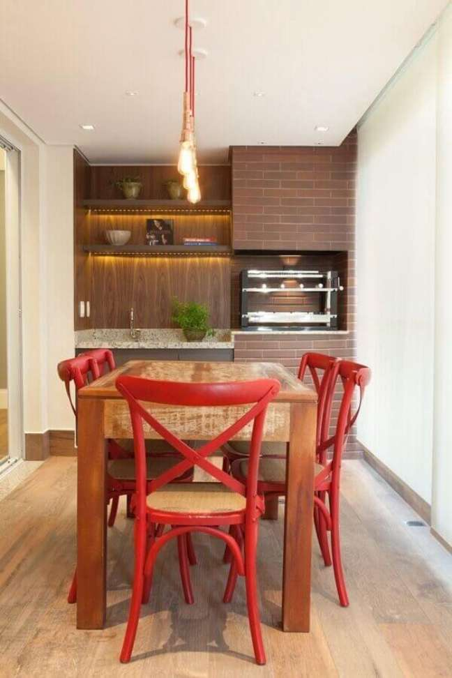 54. Lustre pendente para área gourmet decorada com cadeiras vermelhas para mesa de madeira rústica – Foto: Liliana Zenaro