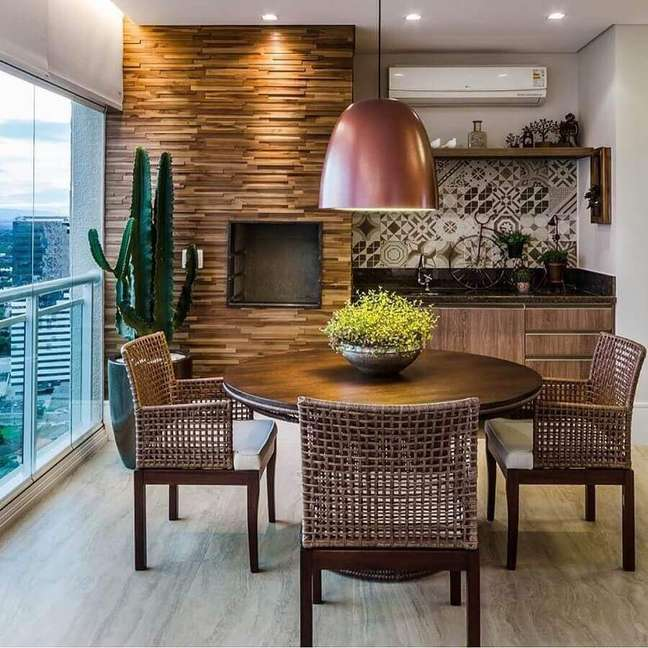 13. Decoração com lustre para área gourmet com revestimento de madeira e mesa redonda – Foto: Pinterest