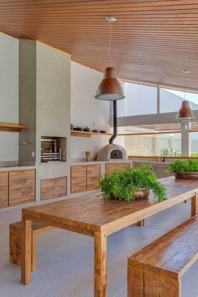 44. Lustre para área gourmet externa decorada com móveis de madeira e forno de pizza – Foto: Pinterest