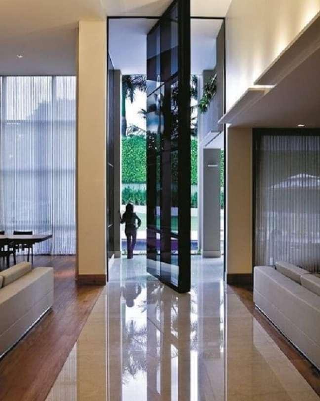 21. Porta gigante e cortinas brancas decoram o imóvel com pé direito duplo. Fonte: Revista Viva Decora 2