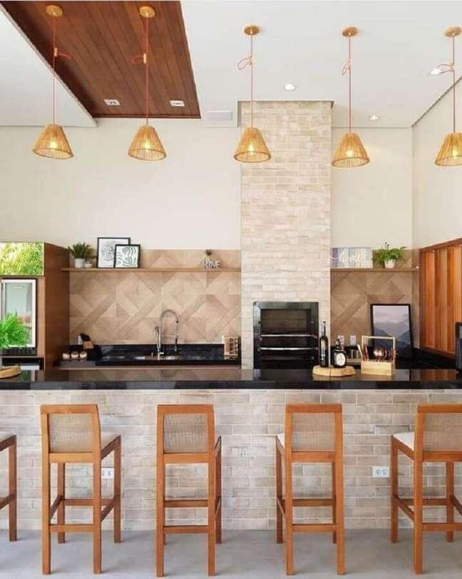 41. Lustre para área gourmet externa decorada com banquetas de madeira – Foto: Fashion Bubbles