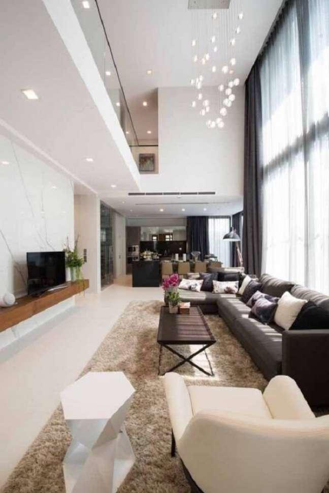 32. O lustre para pé direito duplo traz charme para a sala de estar. Fonte: Pinterest