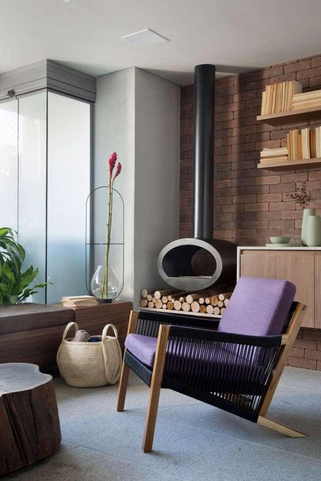17. Lareira suspensa no canto da sala de estar com poltrona roxa moderna – Foto Casa de Valentina