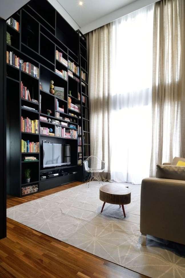 3. A estrutura da estante acompanha o pé direito duplo do imóvel. Projeto de A. M Studio Arquitetura