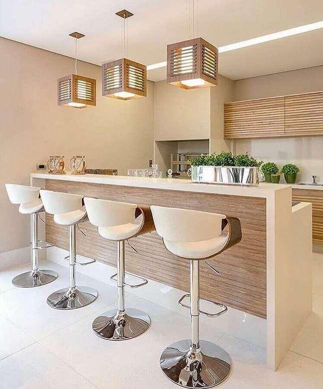 23. Decoração em cores claras com banqueta alta e lustre pendente para área gourmet – Foto: Jeito de Casa
