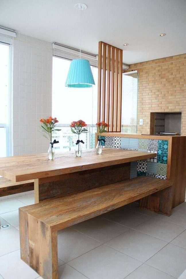6. Decoração simples com lustre para área gourmet com parede tijolinho e churrasqueira – Foto: Pinterest