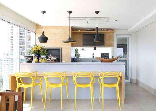 33. Lustre para área gourmet de apartamento decorada com cadeiras amarelas para bancada de madeira – Foto: Karen Pisacane