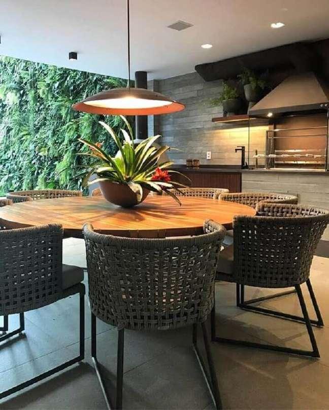 43. Lustre para área gourmet externa decorada com jardim vertical e mesa redonda – Foto: Casa de Valentina