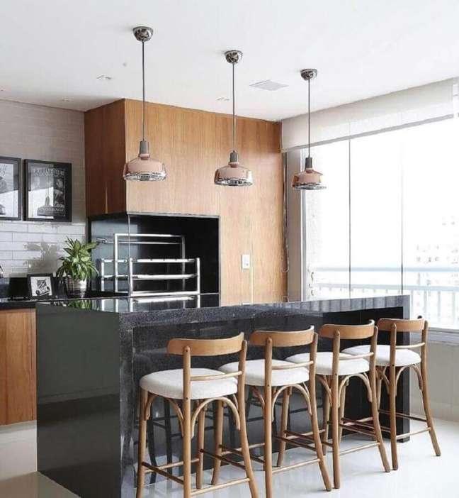 56. Lustre pendente para área gourmet decorada com revestimento de madeira e bancada de preta – Foto: Pinterest