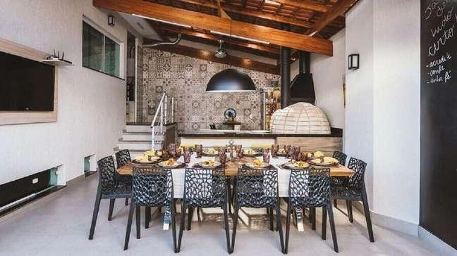 35. Lustre para área gourmet decorada com cadeiras pretas para mesa grande de madeira – Foto: MAV Arqutietura