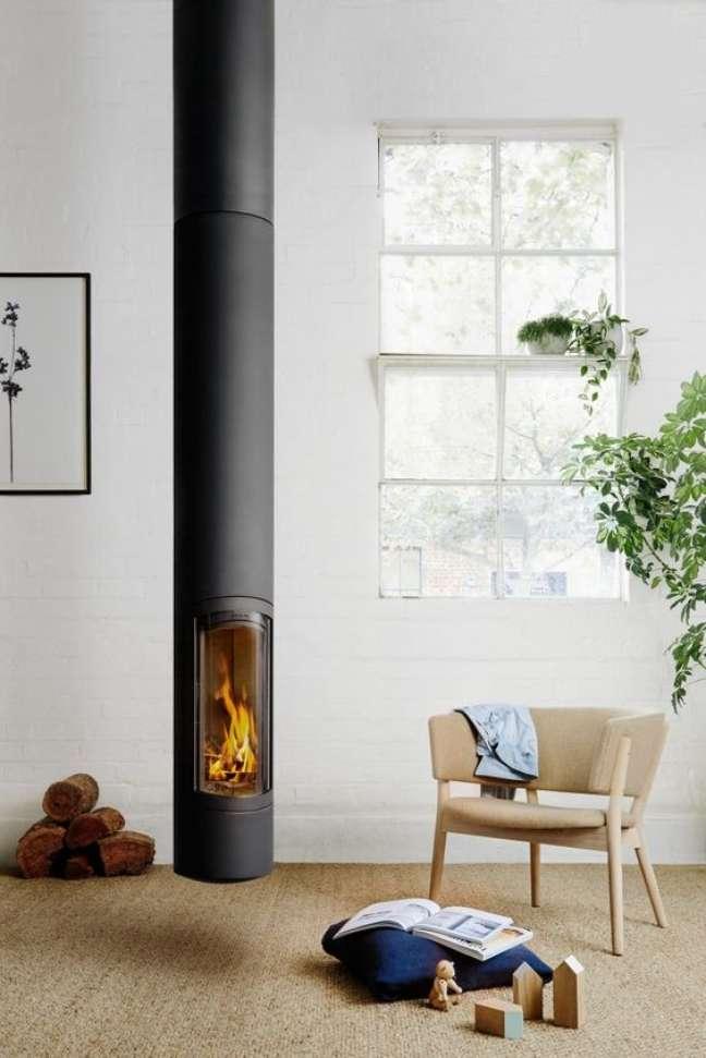 44. Sala moderna com lareira suspensa e poltrona de madeira – Foto Oblica